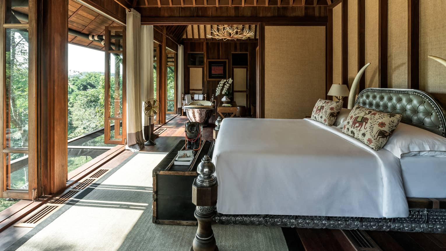 Two-bedroom Explorer's Lodge room bed in front of bright floor-to-ceiling windows