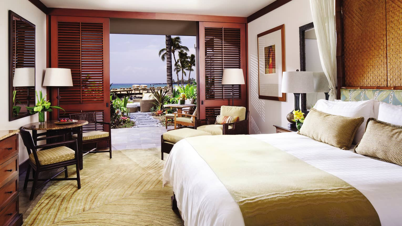 Ocean-View Deluxe Room bed with gold silk sash, pillows, gold chairs by wood patio shutters