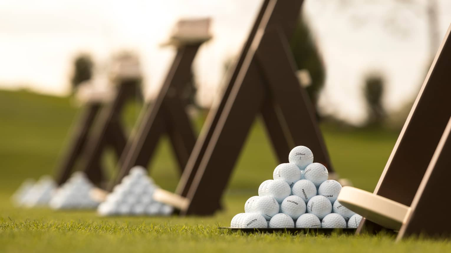 Stacks of white golf balls on lawn in front of wood panels