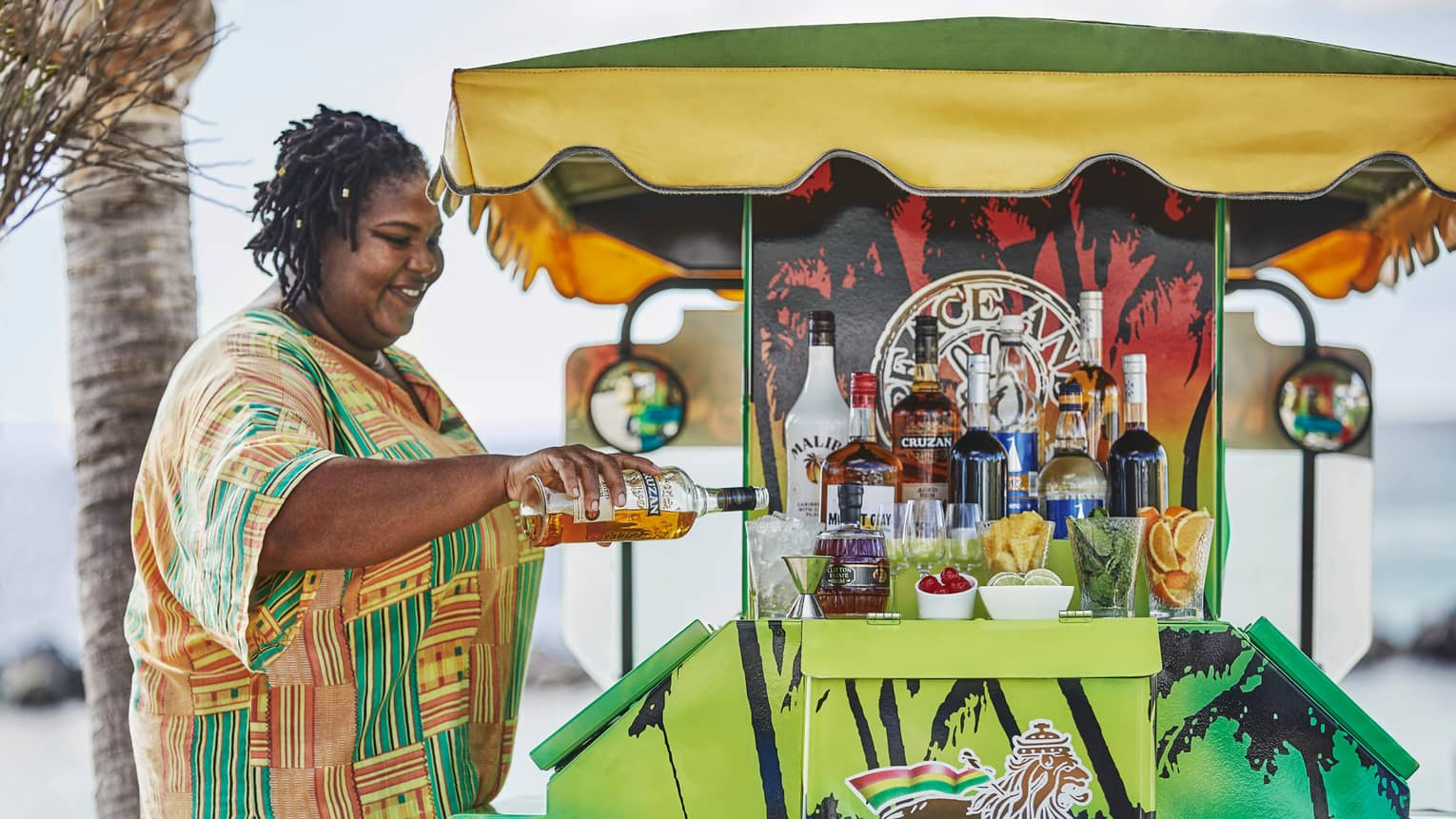 Woman pours rum into cocktail glass with ice at colourful beach cart