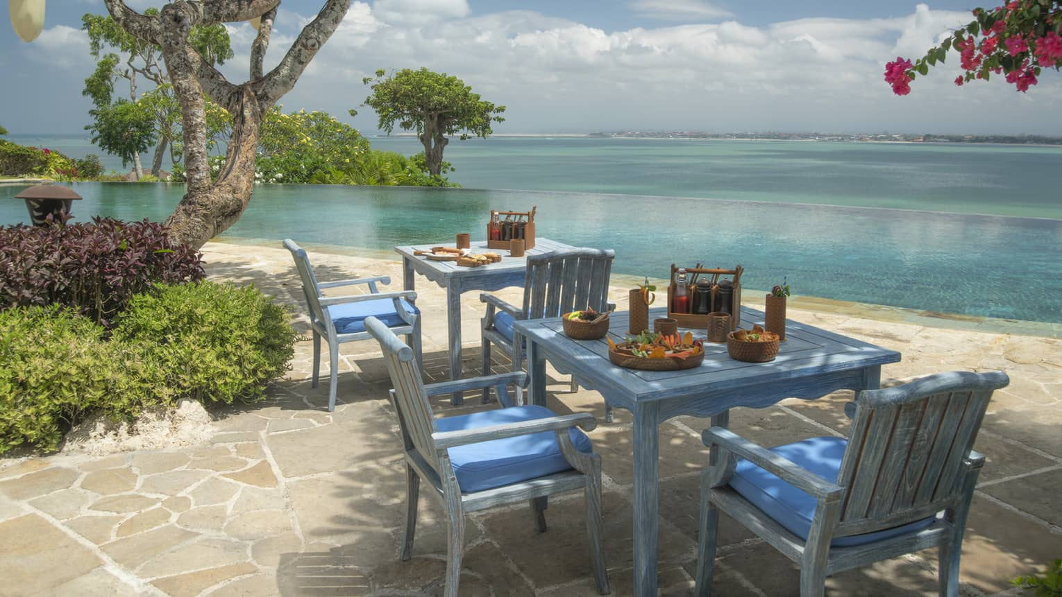 Alu Restaurant blue tables and chairs on flagstone patio directly on beach
