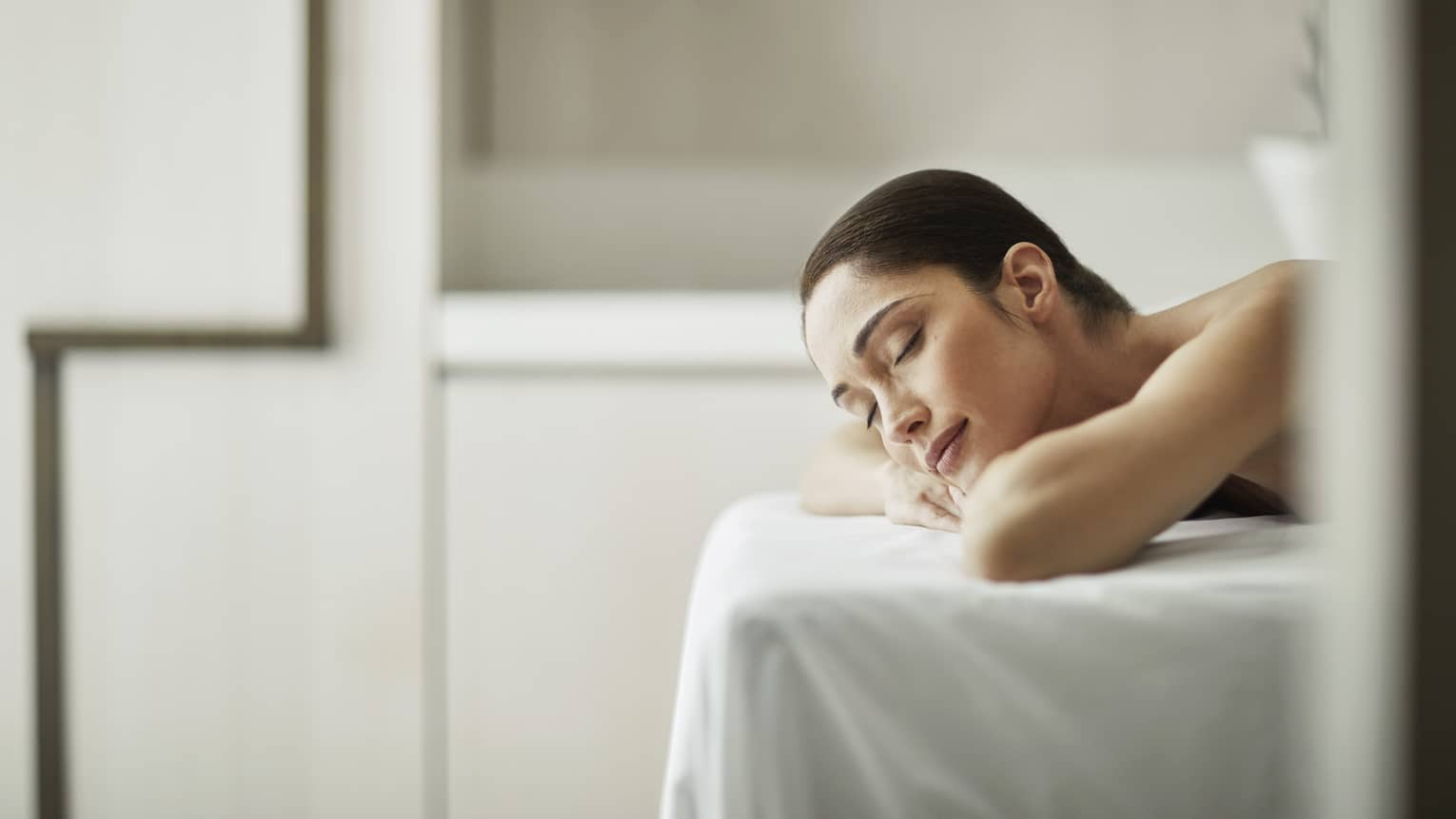 Woman smiles with eyes closed, rests head on arms as she lies on massage table with white sheet