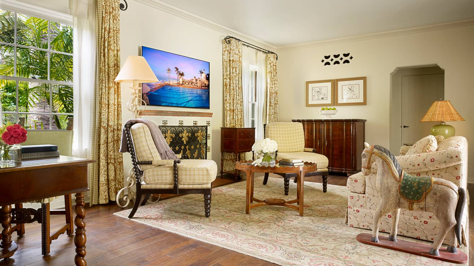 Bungalow Suite sunny living room with yellow plaid accent chairs, floral sofa, rocking horse statue