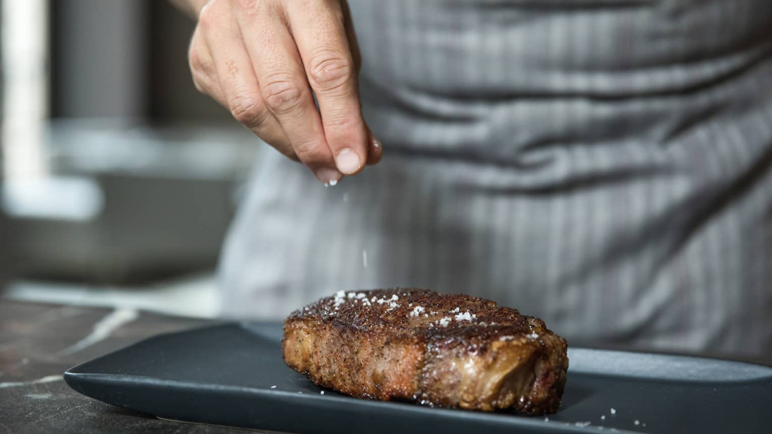 Close-up of chef garnishing salt on thick seared New York steak on black platter