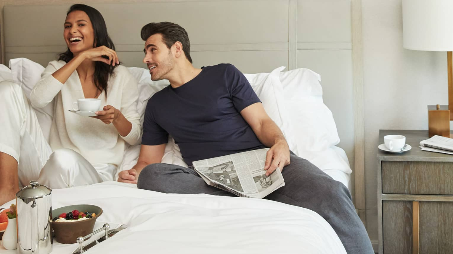 Man with newspaper and woman holding coffee cup lounge in hotel bed with in room breakfast dining tray