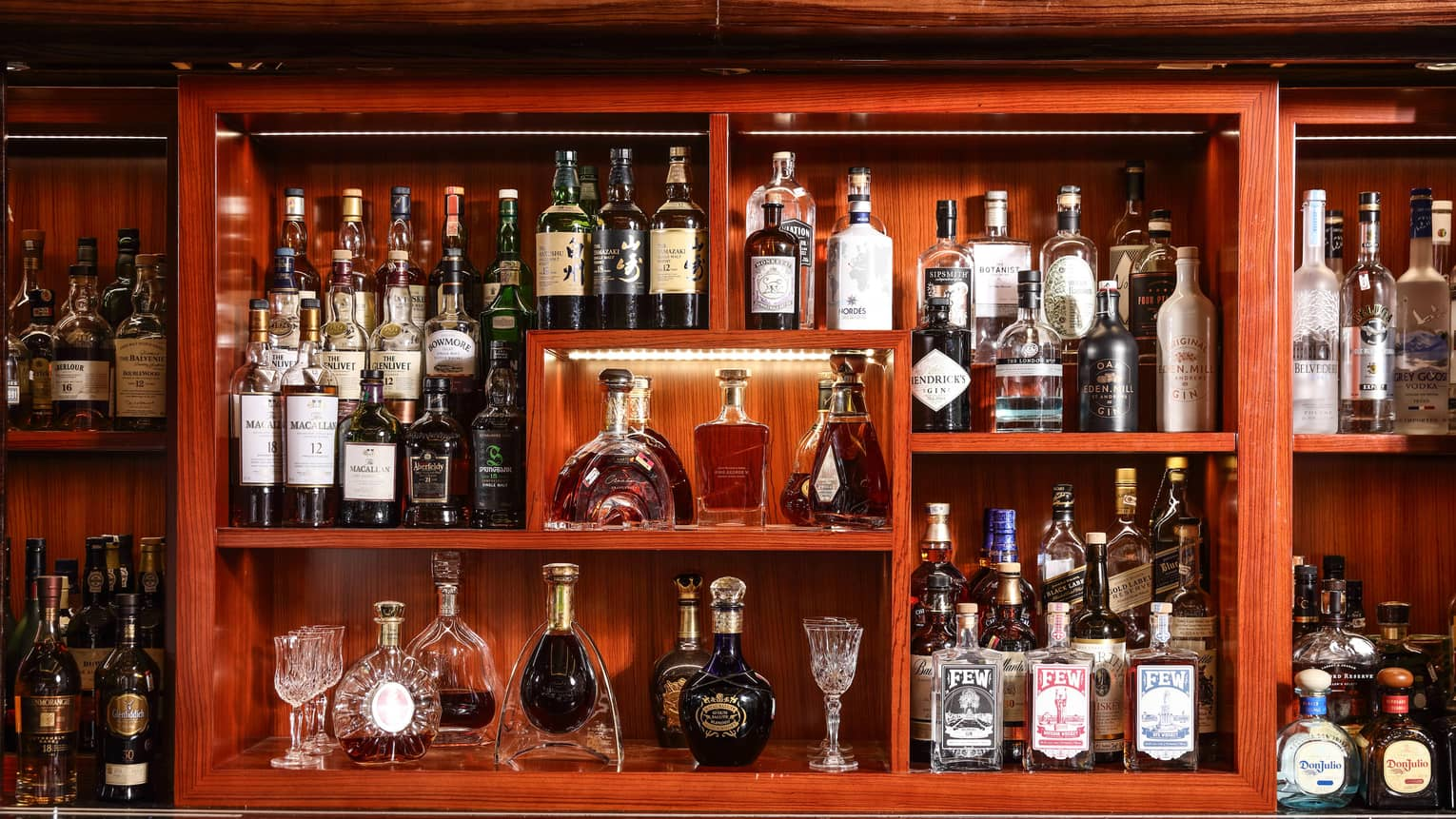 Wood back bar display lined with lights, with rows of liquor bottles