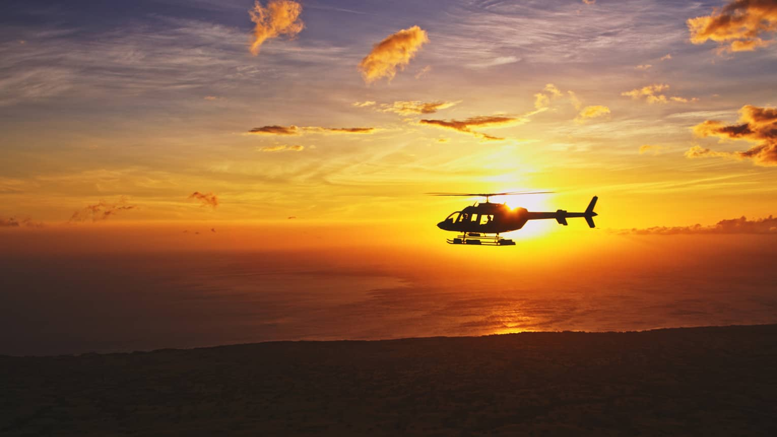 Silhouette of helicopter against orange sunset