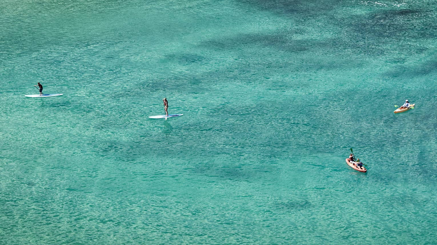 Aerial view of stand-up paddleboarders, boats on lagoon