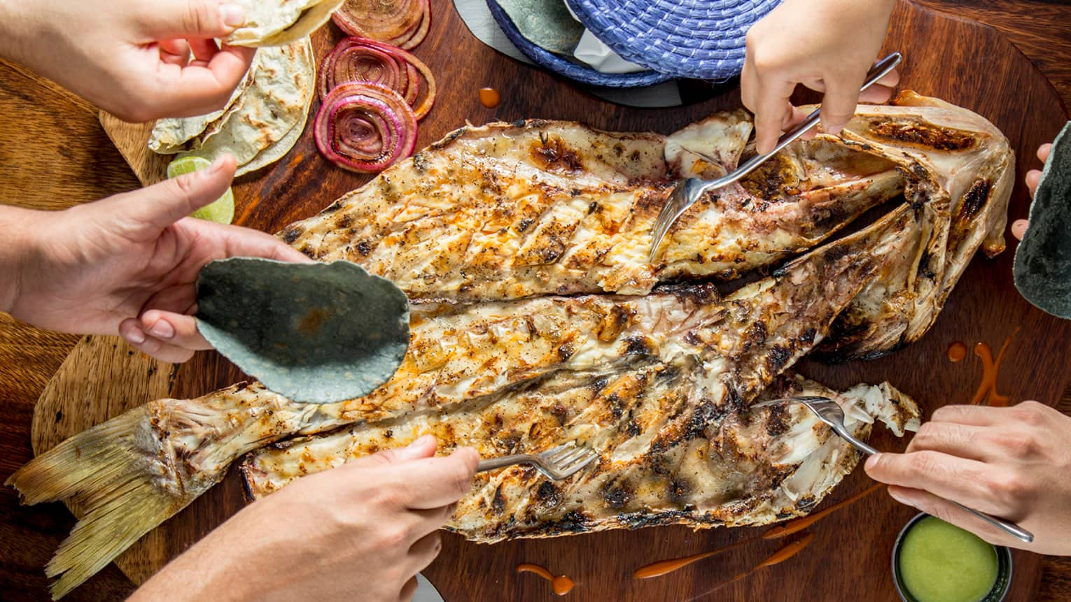 Aerial view of table, hands holding forks, digging into whole grilled fish on platter