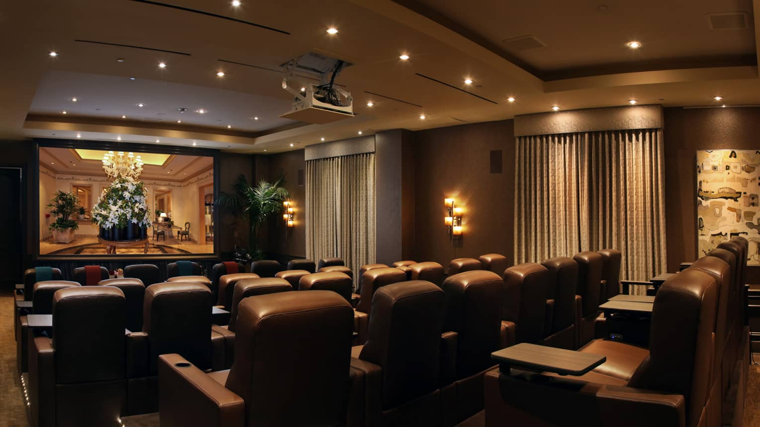 Rows of leather theatre chairs facing screen in movie screening room