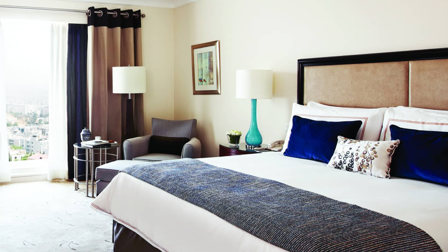 Superior room bed with blue velvet pillows, knit blanket, beige padded headboard, teal lamp, sunny window