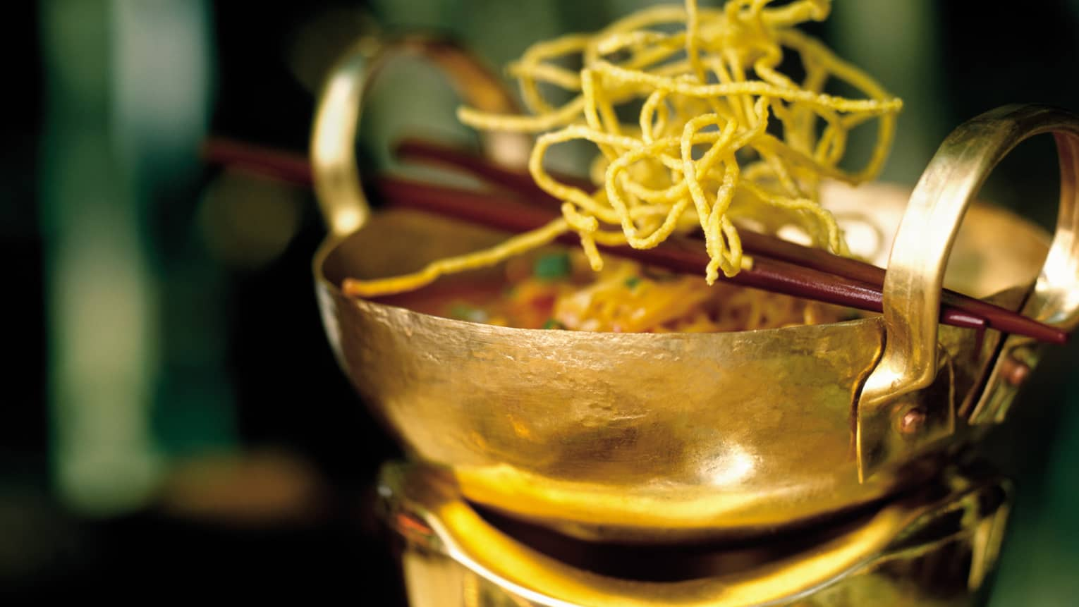 Tom Saab Gai Laotian chicken soup in gold bowl topped with fried noodles, chopsticks
