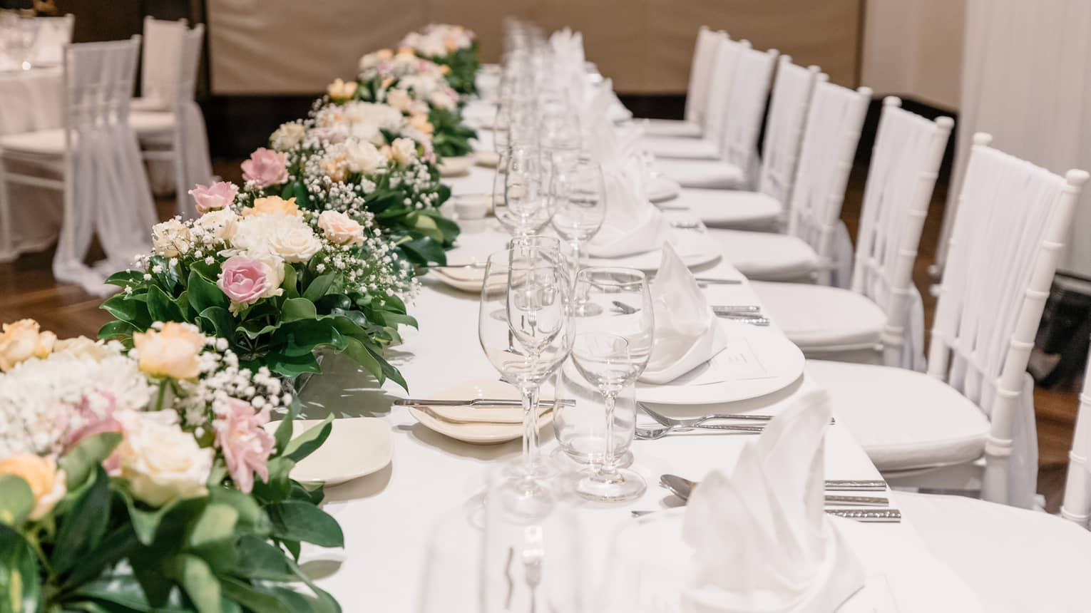 A banquet table is set with a white tablecloth, white porcelain dishes and clear glassware, green, white and pink florals