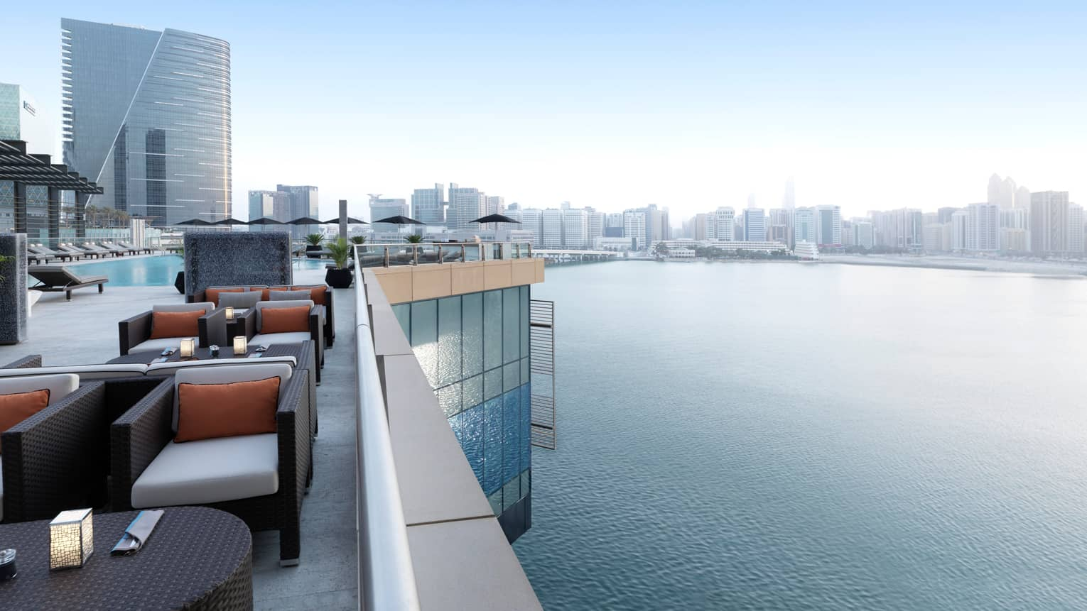 Rooftop lounge with stylish black wicker armchairs, cushions, candles on tables, swimming pool, overlooking Arabian Gulf