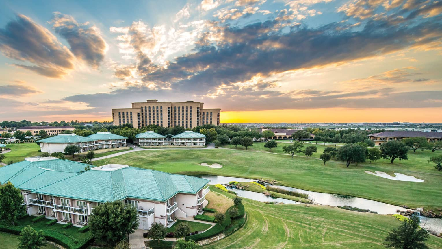 Aerial view of Four Seasons Hotel Dallas, Texas buildings, golf course at sunset