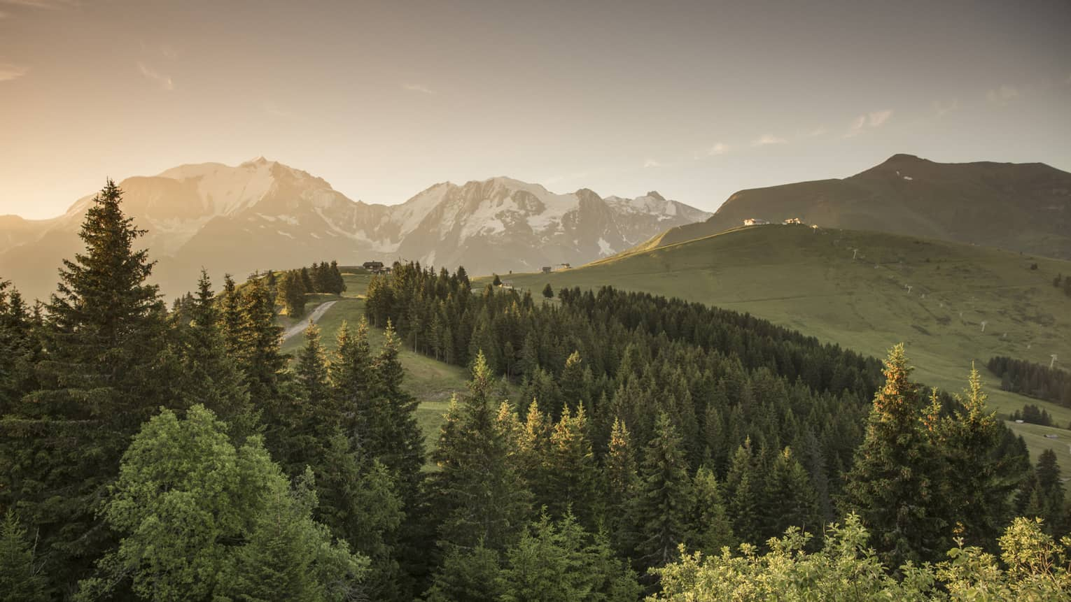 Sun sets over snow-capped mountains, green forests, trails in French Alps