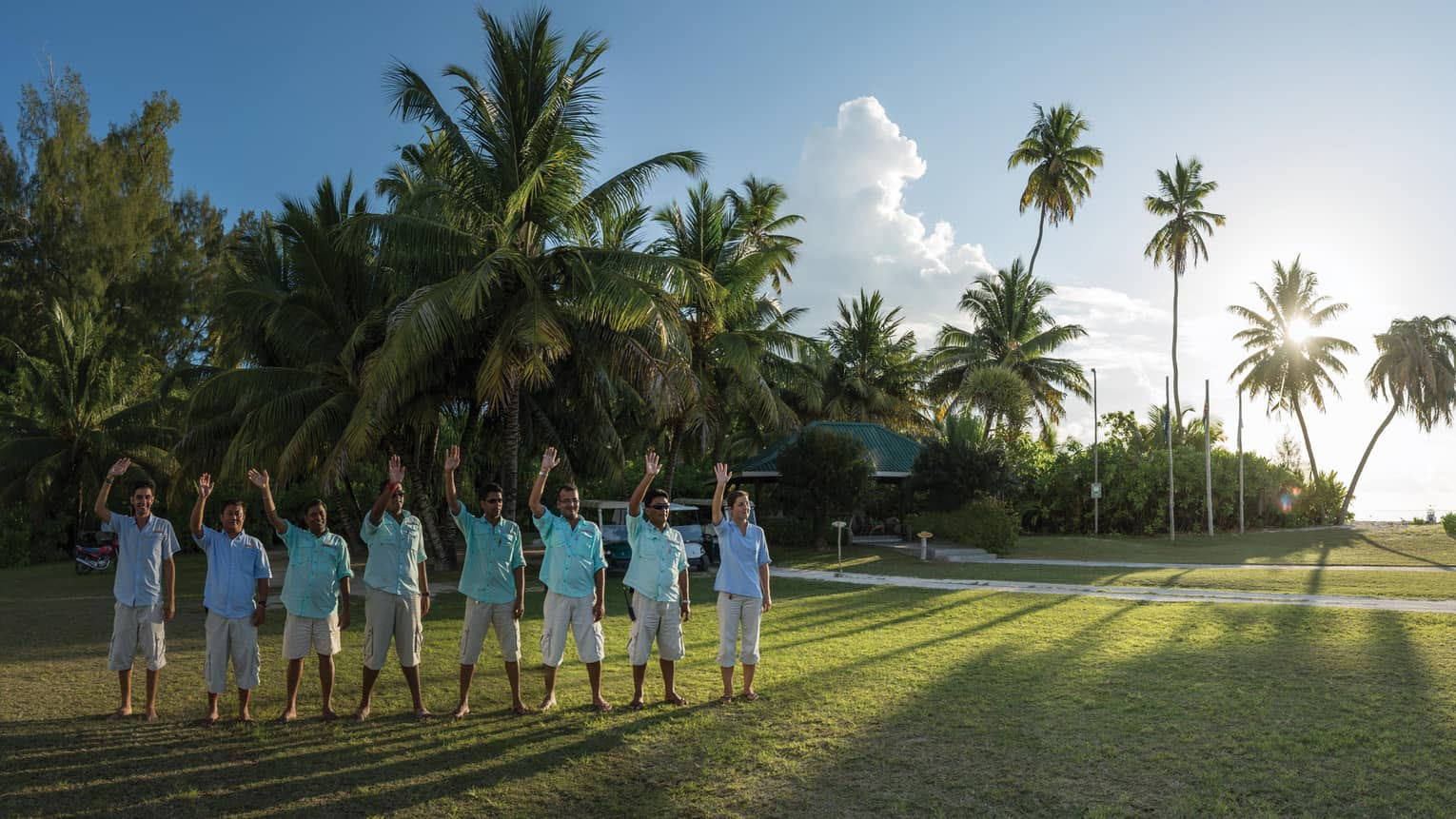 Row of 8 hotel staff in blue button-up shirts wave on green lawn, palm trees in background