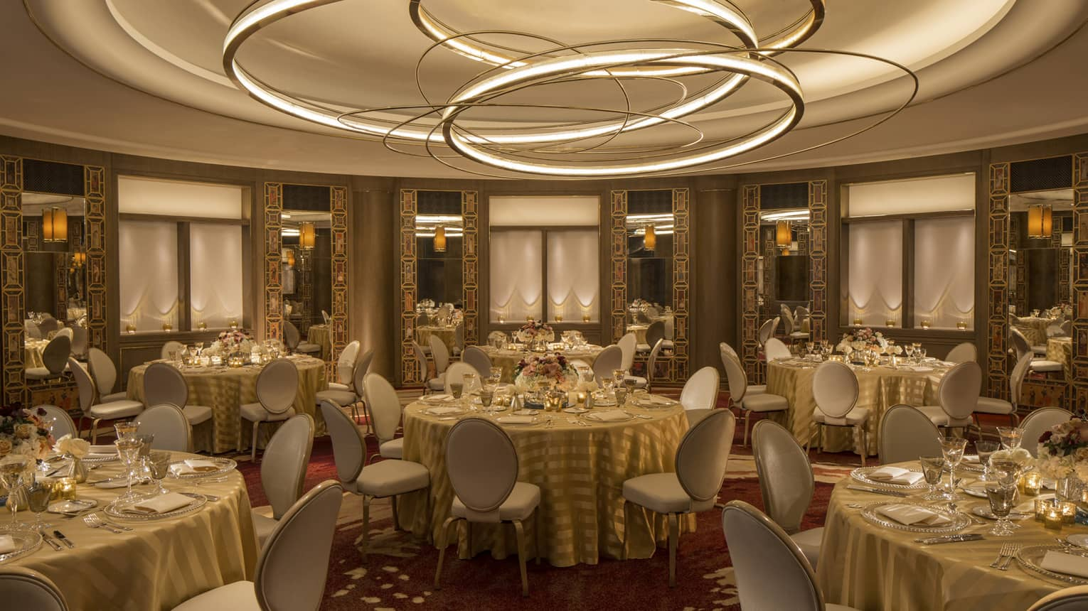 Merchants Hall banquet tables in round event room with recessed ceiling with modern gold disc sculptures