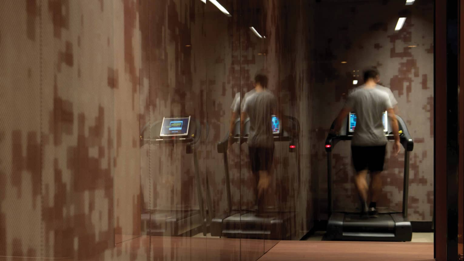 Back of man walking on treadmill in dimly-lit Fitness Centre