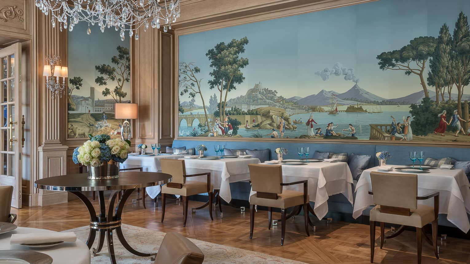 Il Lago elegant Northern Italian dining room with wall-sized mural above tables, chairs, crystal chandelier