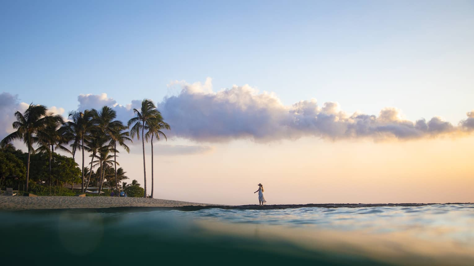 A woman walks along the beach at sunrise with palm trees on the sand