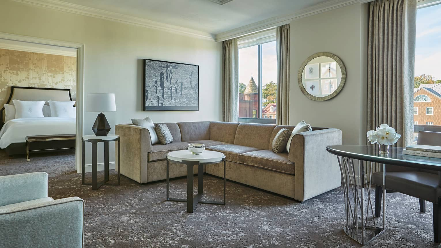 Georgetown One-Bedroom Suite L-shaped grey sofa between door to bedroom, large picture windows, work desk
