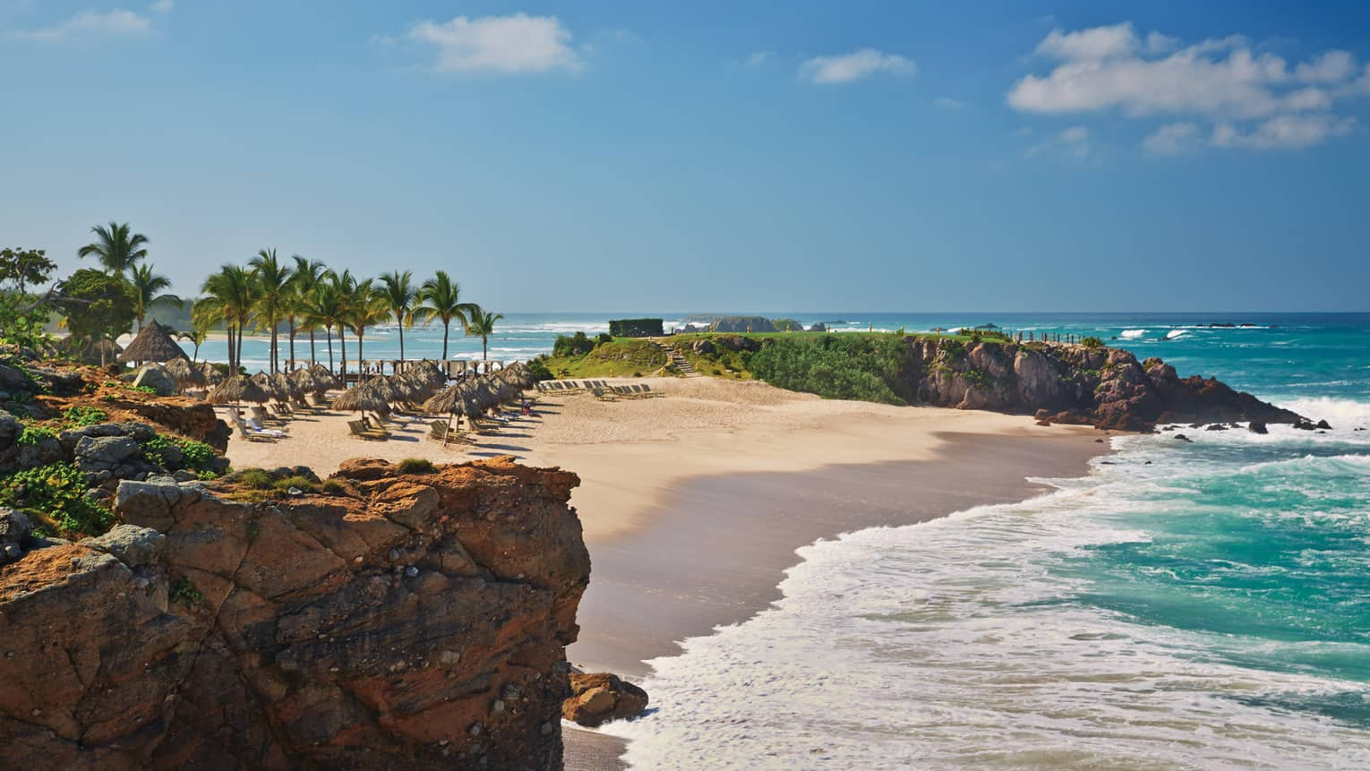 White sand beach lined with lounge chairs, palms, turquoise tides from oceanside cliff