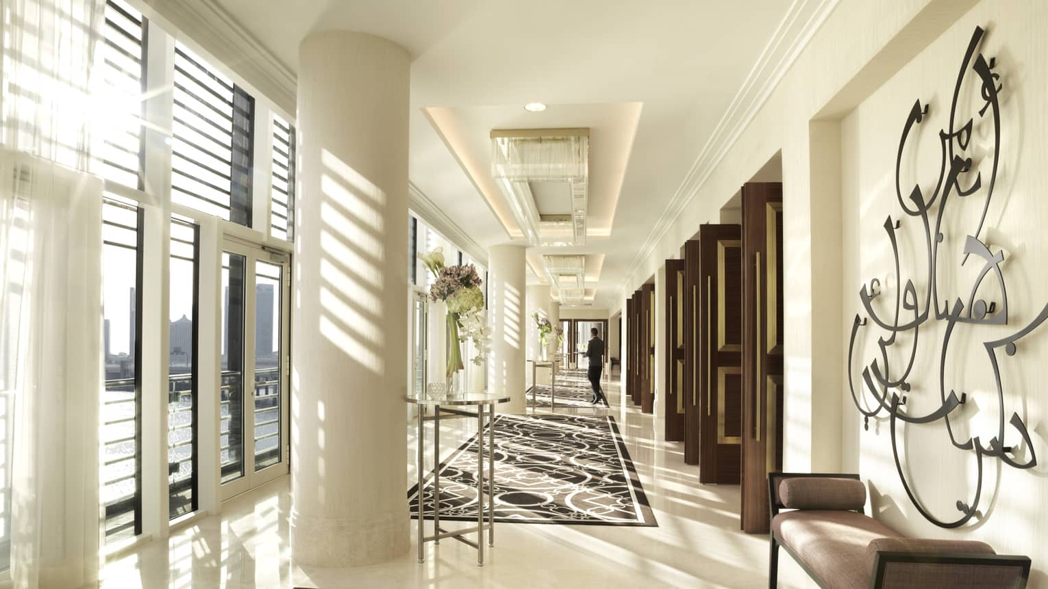 Sunlight streams into bright Al Maryah Ballroom event space with white marble pillar, hall
