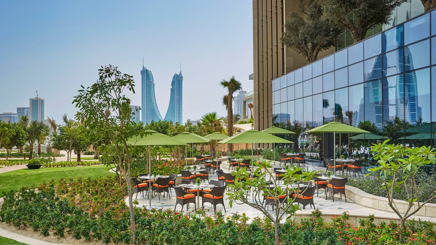 Bahrain Bay Kitchen outdoor patio tables, umbrellas, surrounded by green gardens, lawn