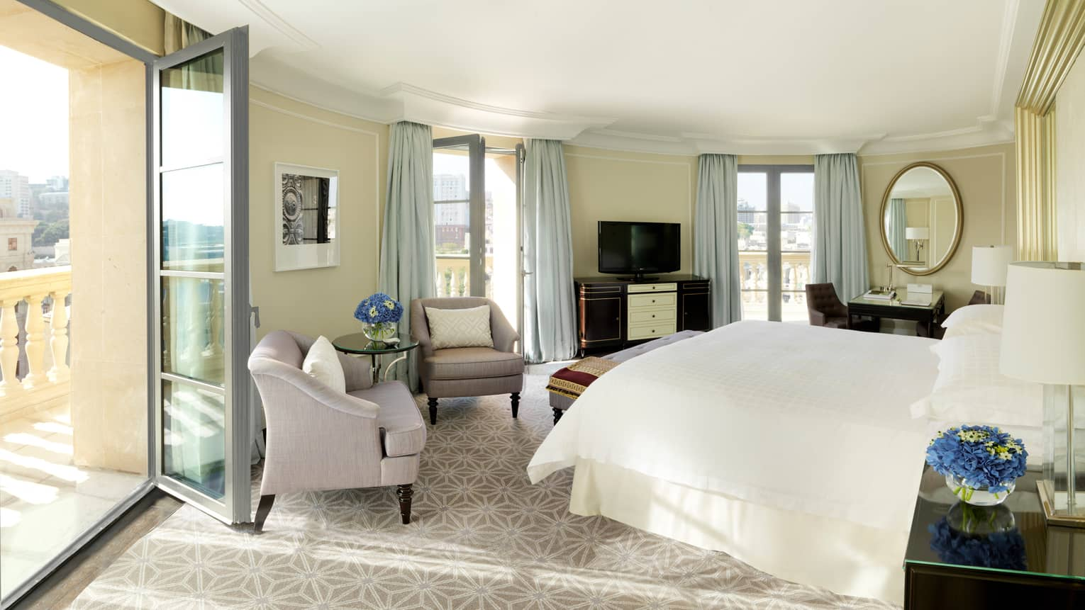 Hotel bedroom with a white king bed, two light purple arm chairs, and three glass doors opening to balcony