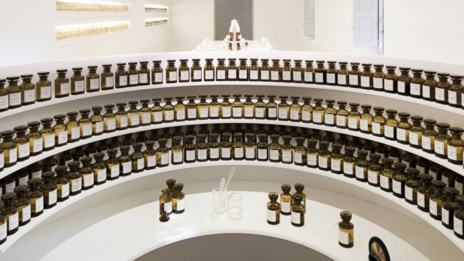 Curved white shelves with small glass tincture bottles at the Fragonard perfume factory