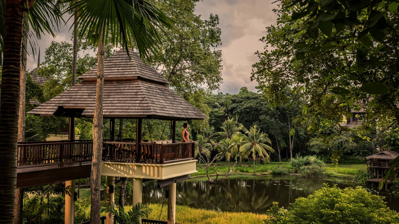 Woman stands at edge of balcony under shingled-roof, overlooking pond and tropical gardens