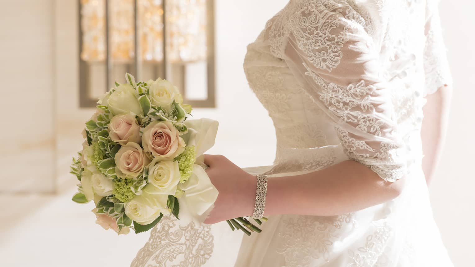 Bride wearing lace wedding gown stands by sunny window, looks down at rose bouquet