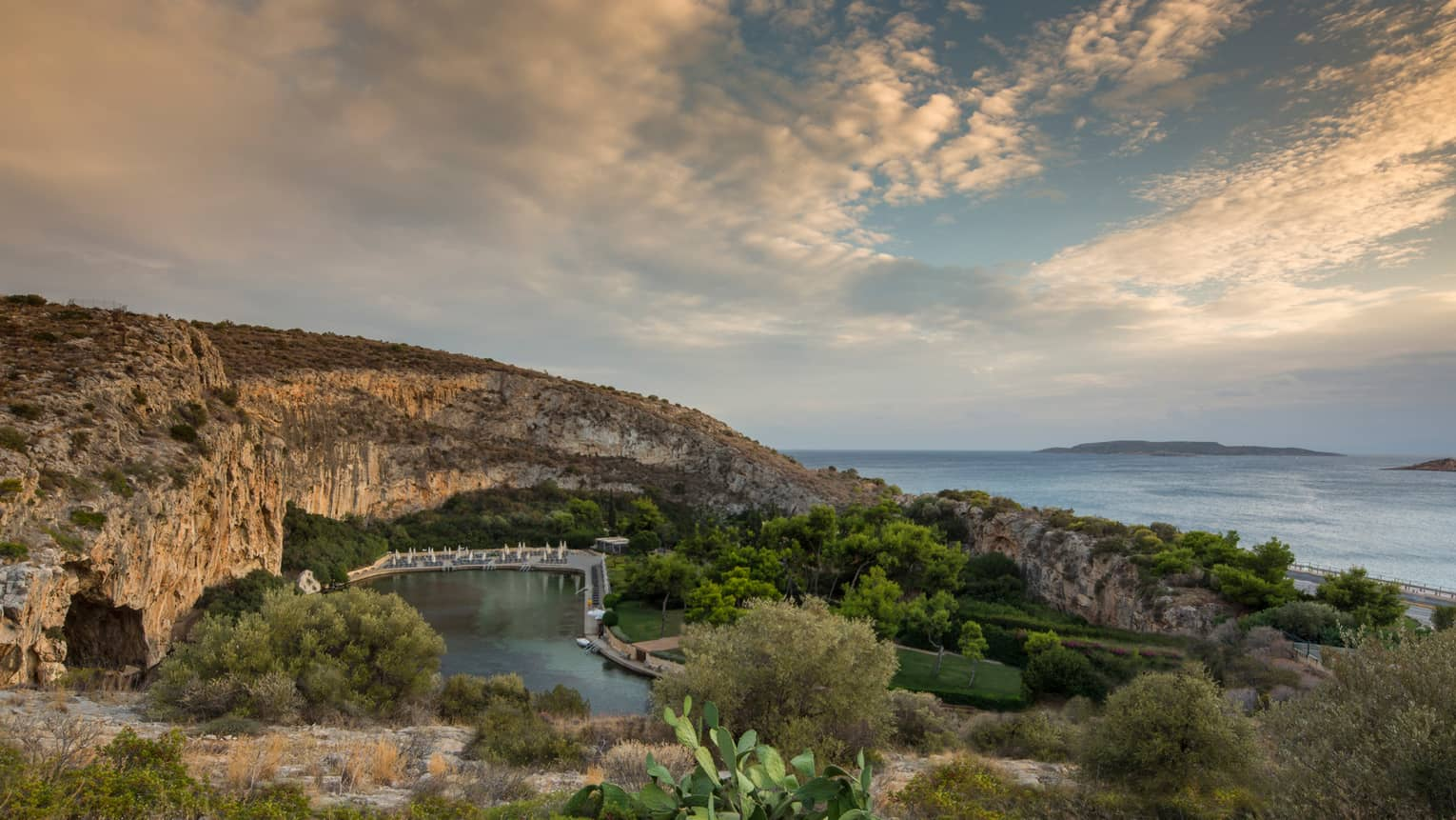 View of Vouliagmeni with rocky hill, green trees and shrubs overlooking ocean