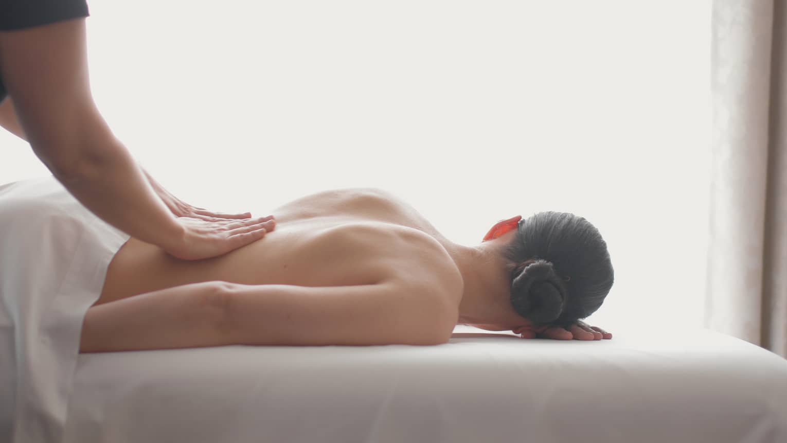Side view of woman lying on massage table, hands massaging her bare shoulders