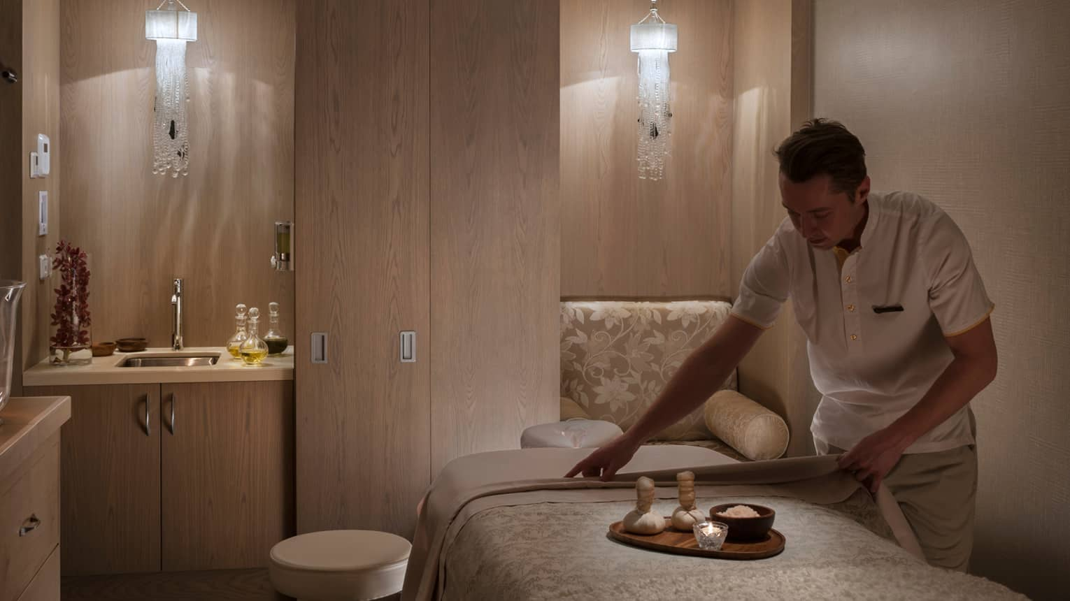 Spa staff in uniform places tray with candle votive, bowl of salt on massage bed