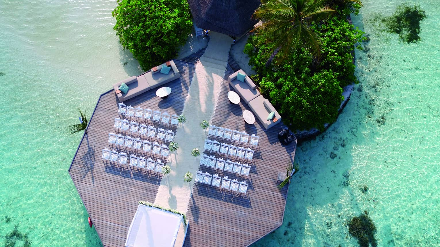 Aerial view of wedding ceremony, rows of white chairs on dock over lagoon