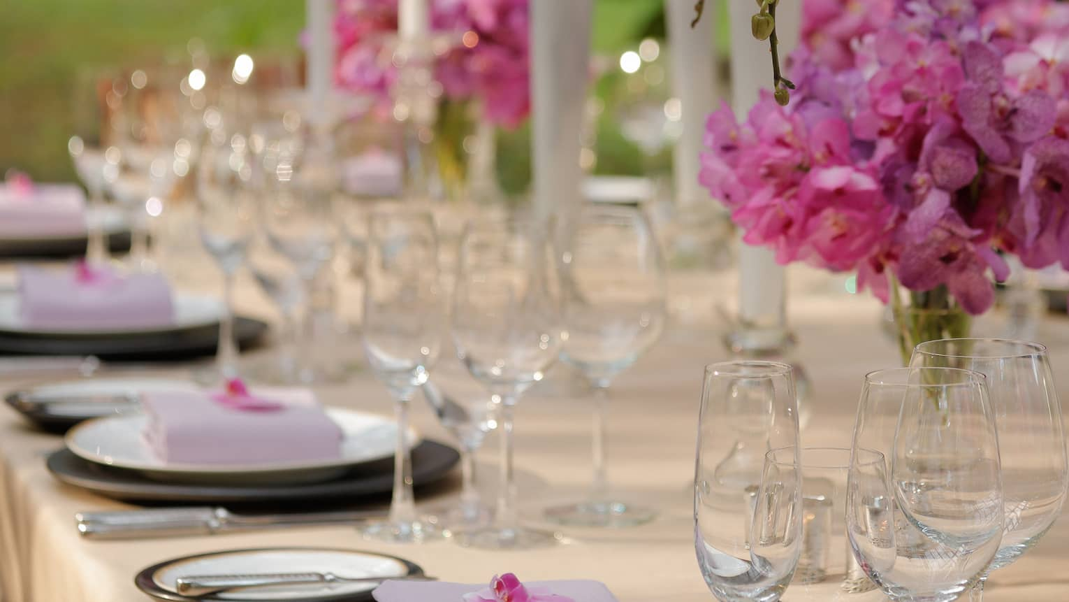 Outdoor dining table with pink flowers in vases, tall white candles