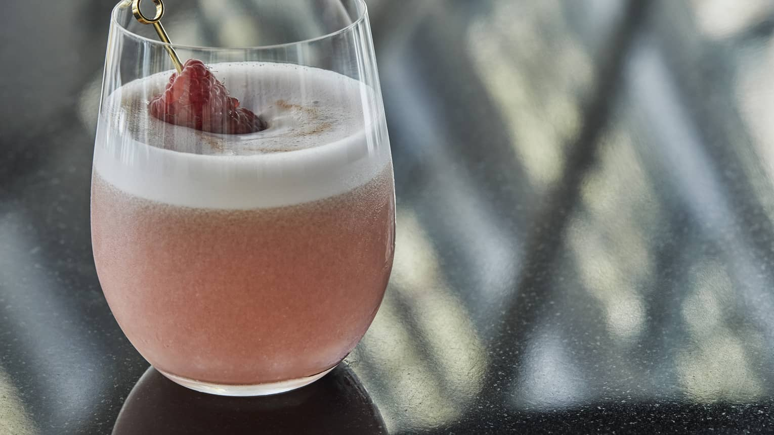 A pink fizzie cocktail garnished with a strawberry