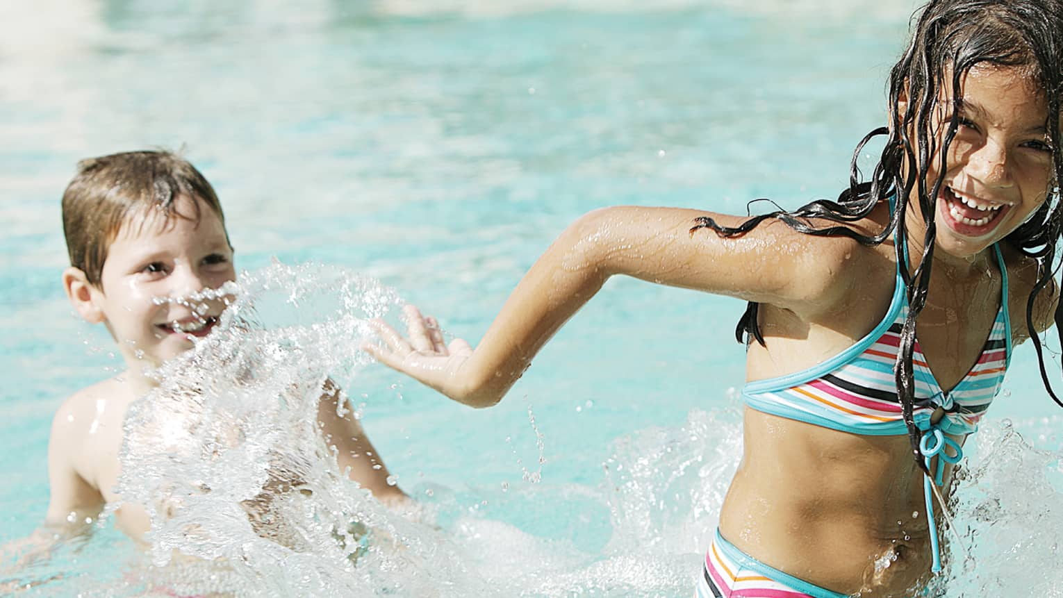 Laughing girl in swimsuit plays in swimming pool, splashes smiling boy