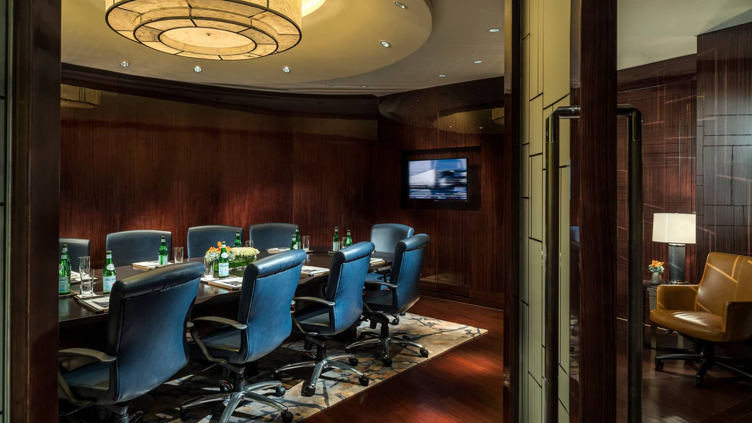 Business Centre meeting table with tall leather chairs, TV screen
