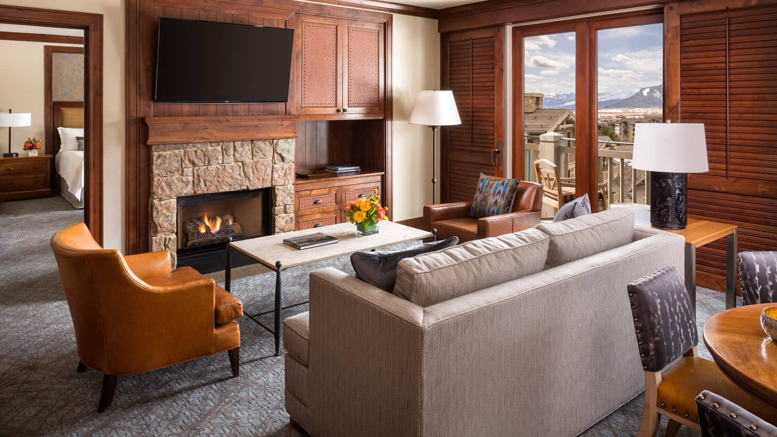 Mountain-View Suite back of sofa, orange armchair by stone fireplace and fire, TV, bedroom door