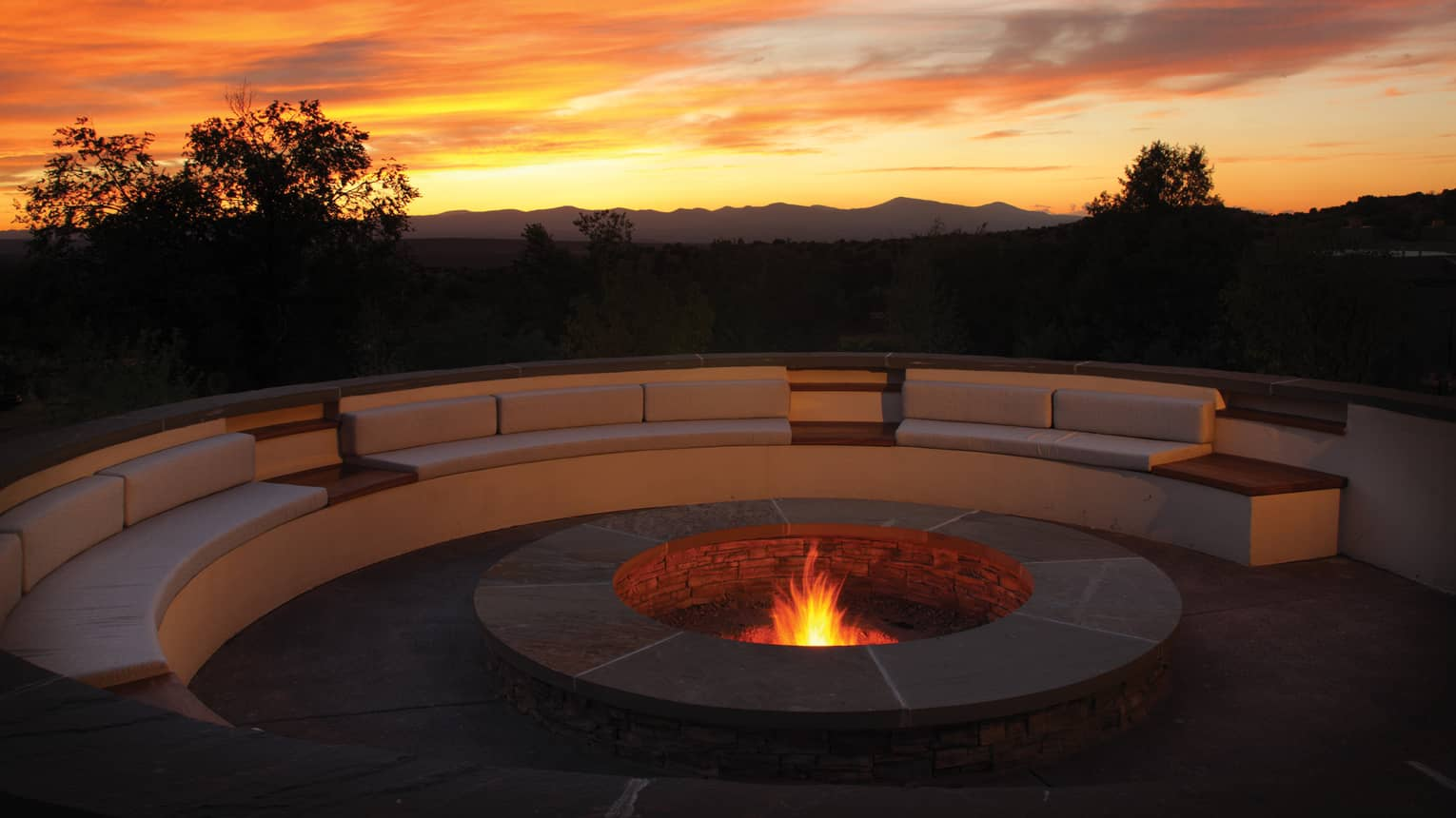 Outdoor fire pit burning with a large curved sofa, colourful sunset in the sky