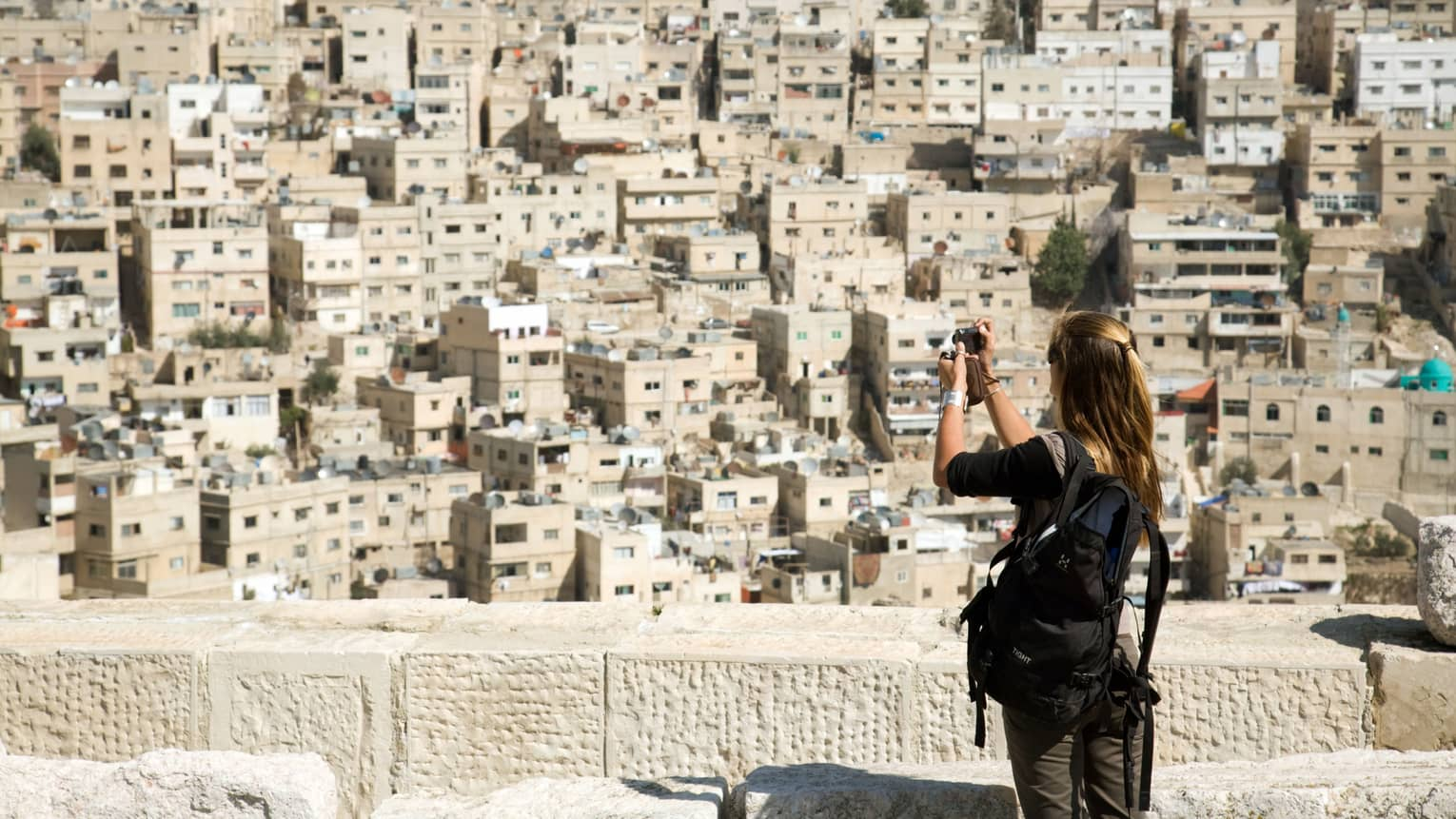 Woman takes photo at ledge overlooking Amman city buildings
