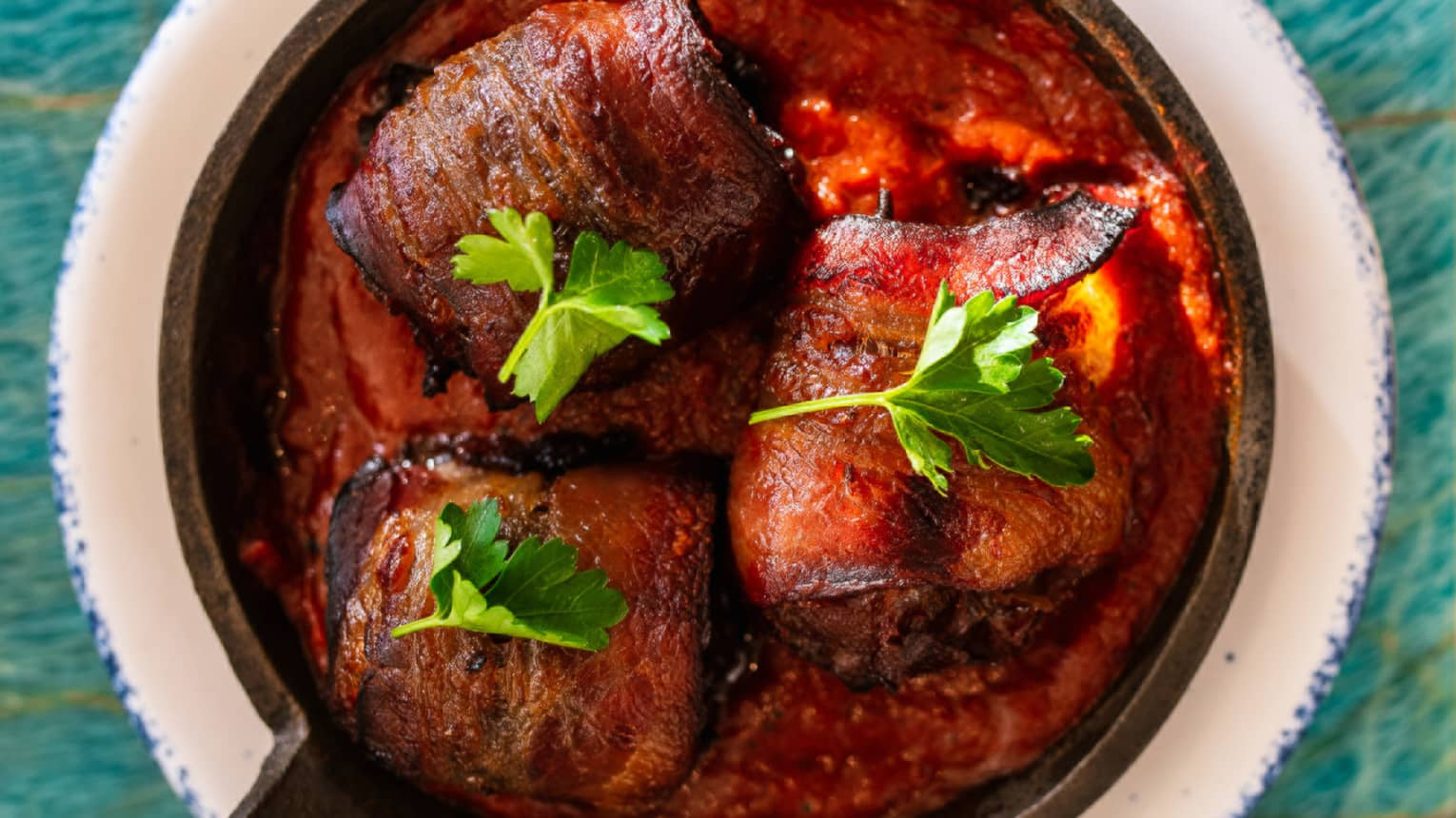Skillet of bacon-wrapped, stuffed dates with chorizo and aji panca sauce, topped with parsley