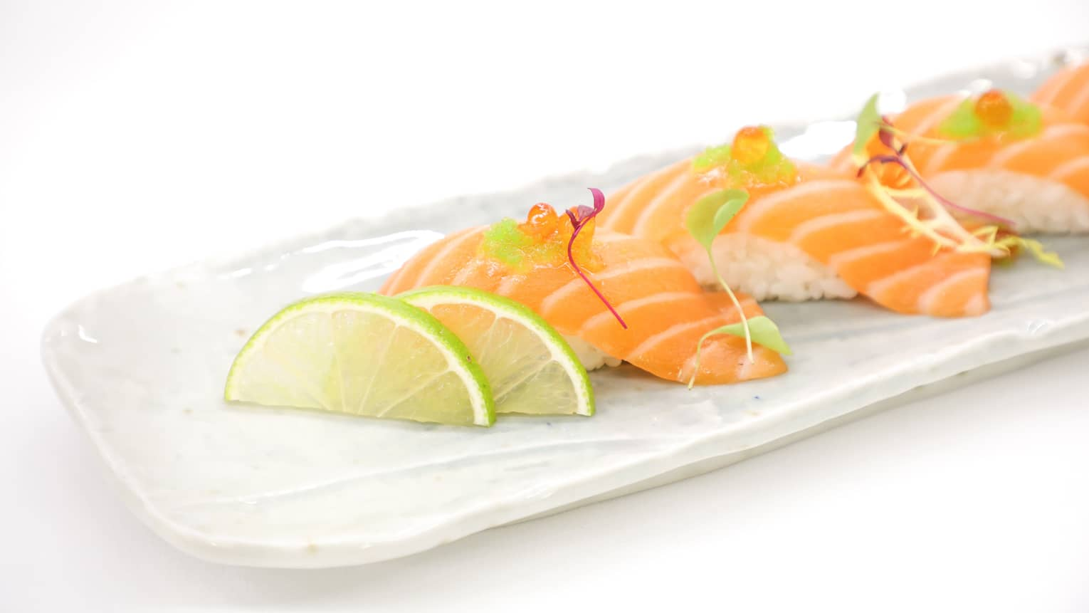 Slices of salmon sashimi on white tray with lime wedges