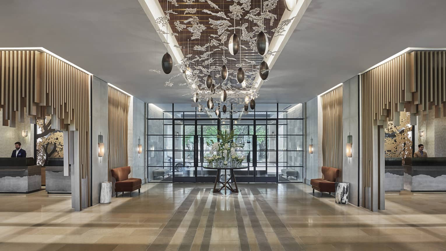 Delicate glass and rounded lights adorn the ceiling of a well-lit lobby