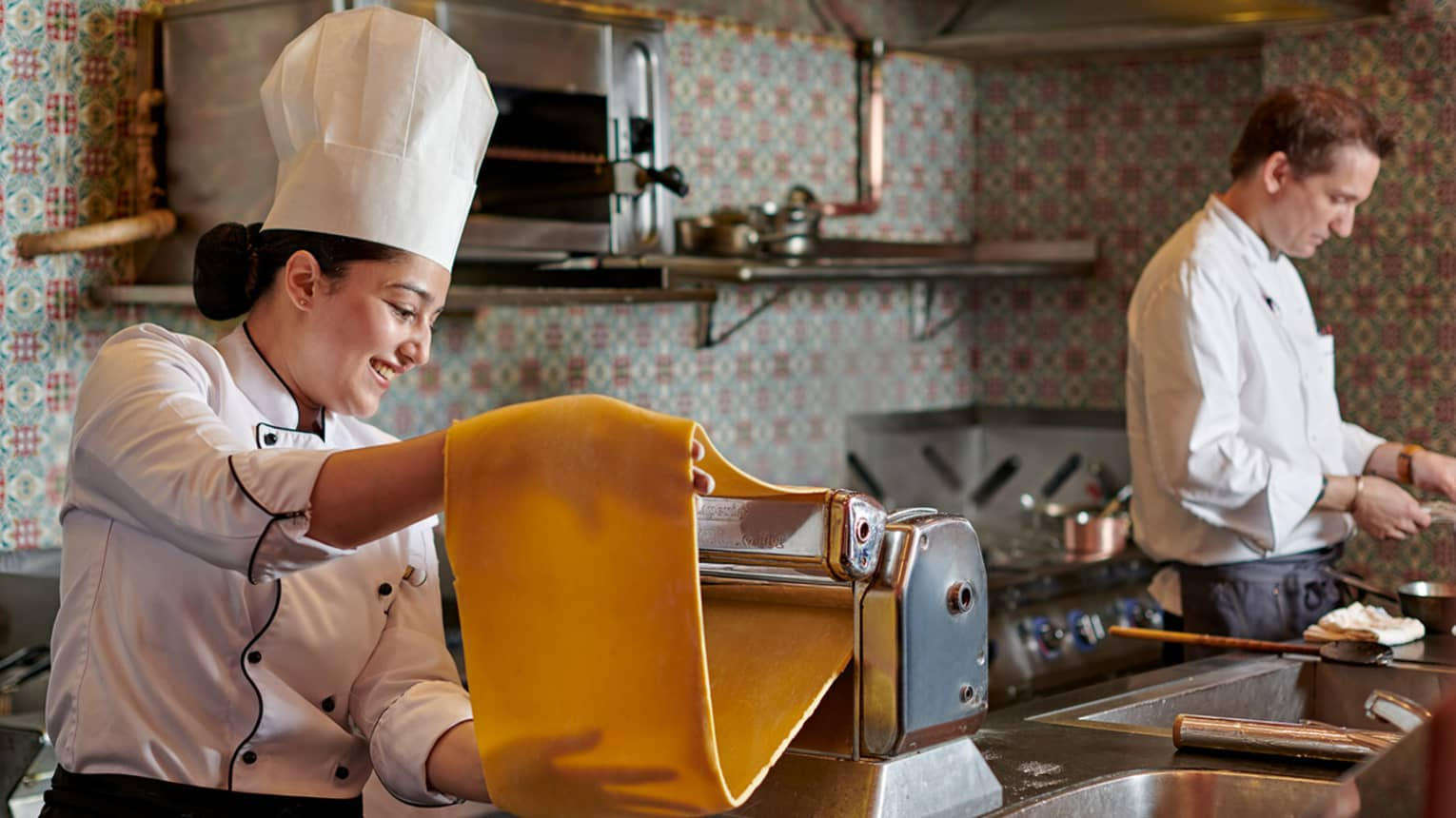 A woman wearing tall white chef's hat makes pasta, feeding dough through a rolling machine