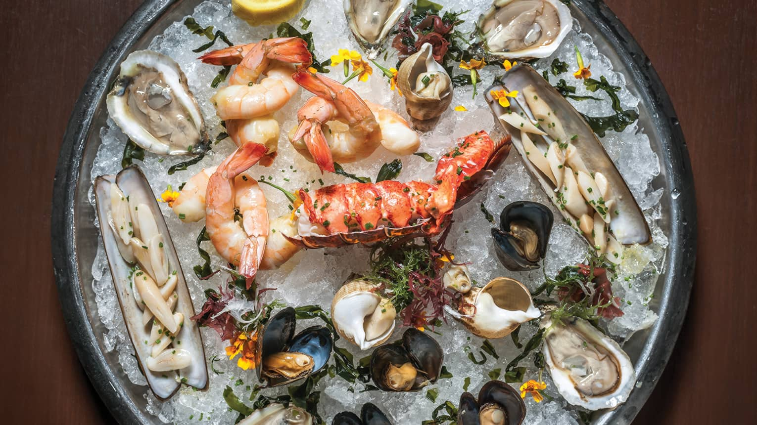 Shellfish, shrimp, oysters on ice on round silver tray
