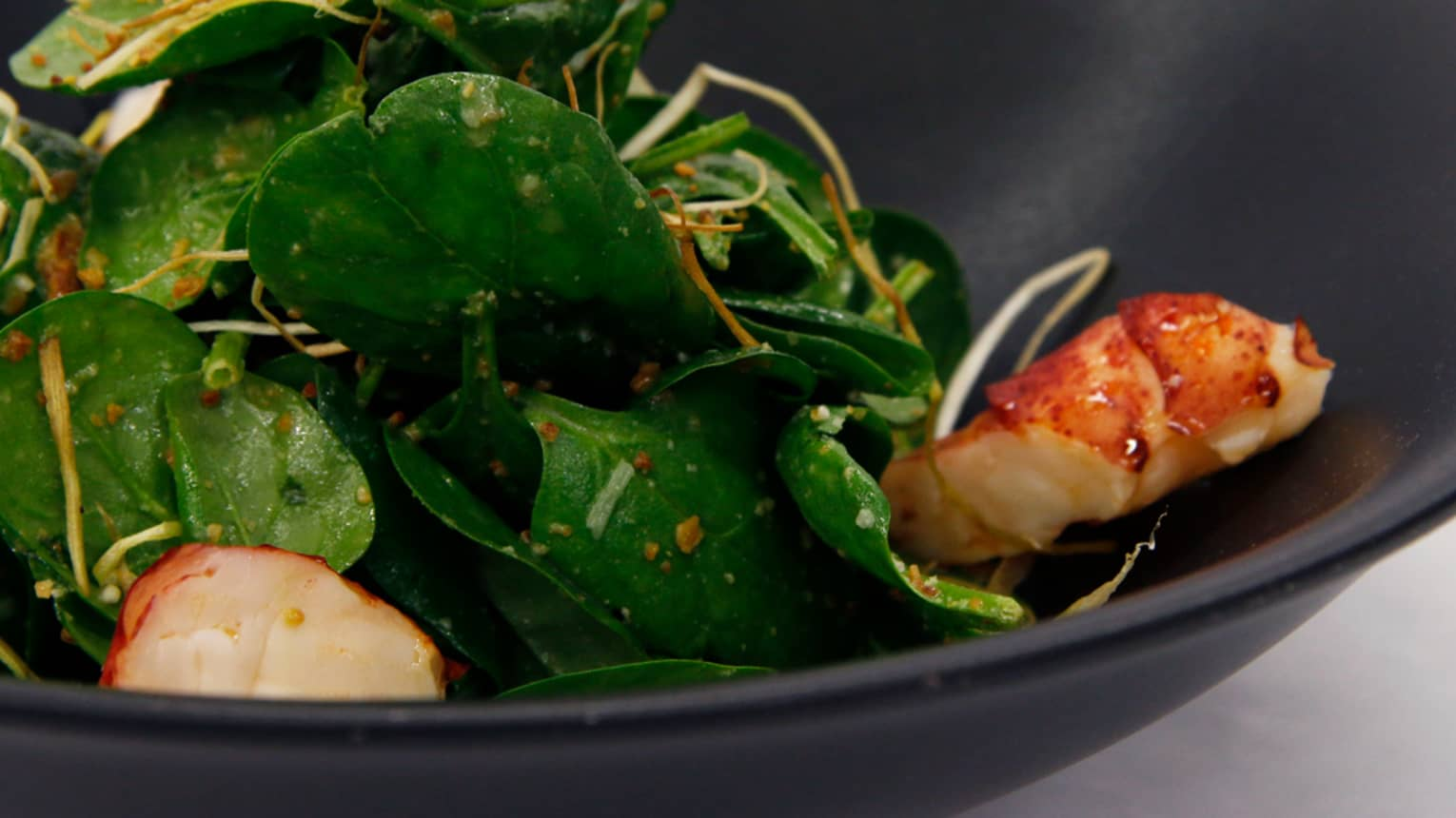 Close-up of Lobster and Spinach Salad with chunks of lobster meat with green leaves, vinaigrette